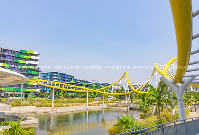 Yellow wave-like architectural feature around pond with modern green and blue designed apartment buildings