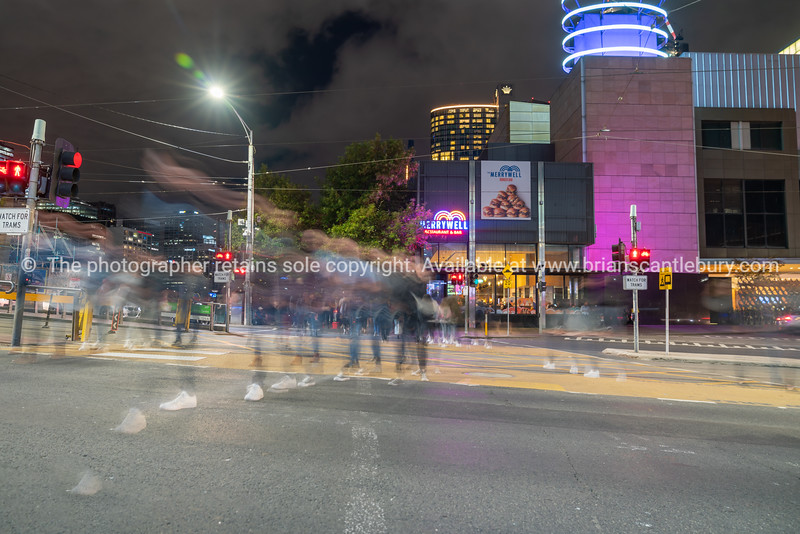 City street scene in long exposure with blurred shapes and colours of passing vehicles and people against illuminated buildings.