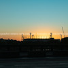 Melbourne Cricket Ground stadium silhouetted by bright rising morning sun.