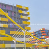 Yellow wave-like architectural feature in foreground of modern yellow and orange colored and  designed apartment buildings