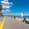 Promenade along St Kilda beach with people out enjoying summer and beach.