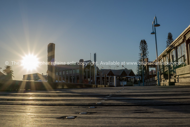 Sun flare over wooden wharf decking and building around harbour waterfront at sunset.