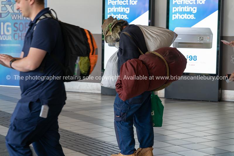Senior man carrying bags wearing old hat walks along