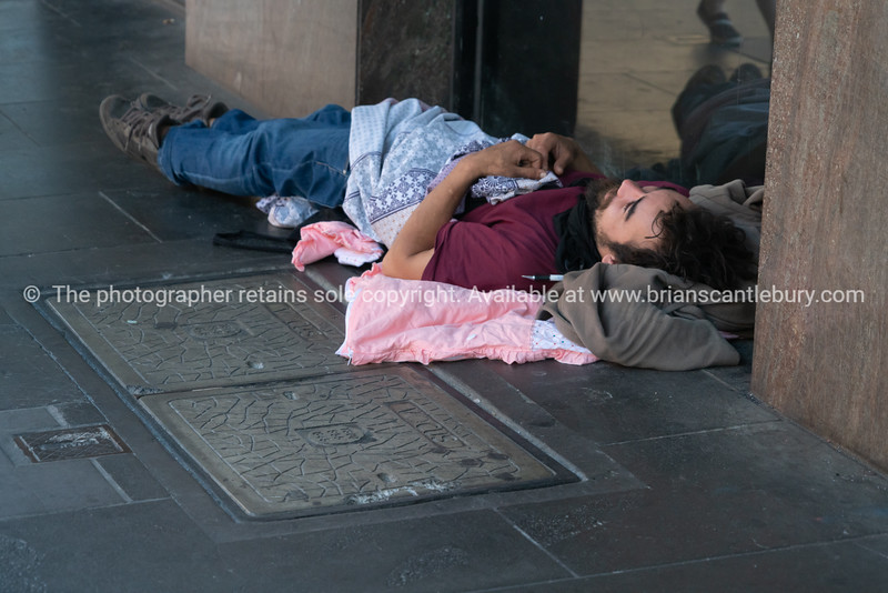 Homeless man asleep in in doorway in city street.