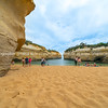 Tourists enjoying and visiting the beach between high limestone walls enclosing bay in Loch Ard Gorge.