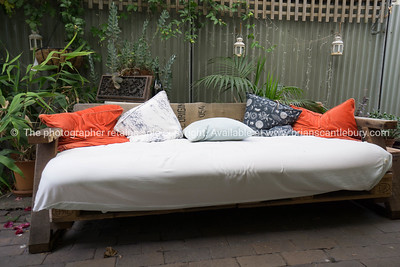 Comfy devan with orange and blue cushions in home conservatory.