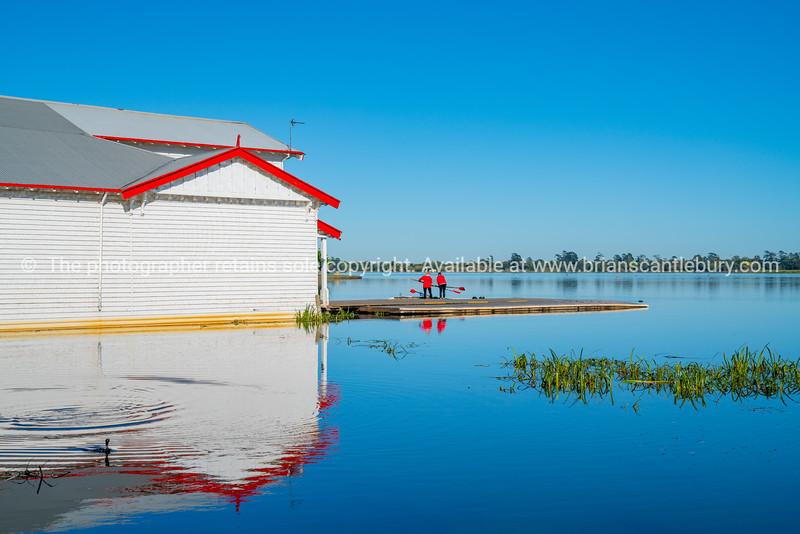 Boatshed building reflected in calm blue Lake Wendouree, Ballarat Australia.