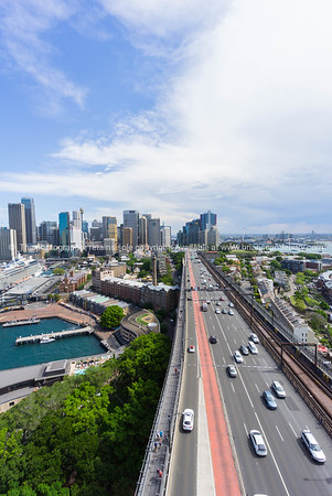 Vehicles cruise along Cahill Highway that projects straight ahead into distance and city skyline with Sydney Harbor of left, Australia