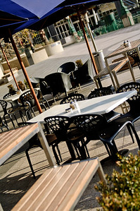 Dining tables set up outside on the sidewalk at a cafe in Melbourne.