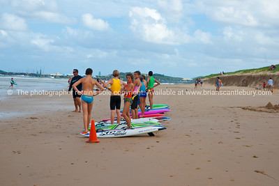 Junior lifesavers in traing. Standing with boards. Model released; no, for editorial & personal use.