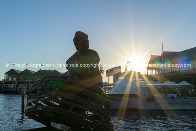 Sun flare and silhouette  bronze fisherman with traps statue and building around harbour sunset.waterfront