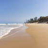 Long sandy beach with distant people and buildings of Surfers Paradise.