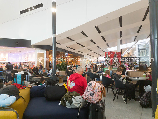 People sitting around cafe tables and lounge chairs heads down using devices with baggage scattered about in airport terminal