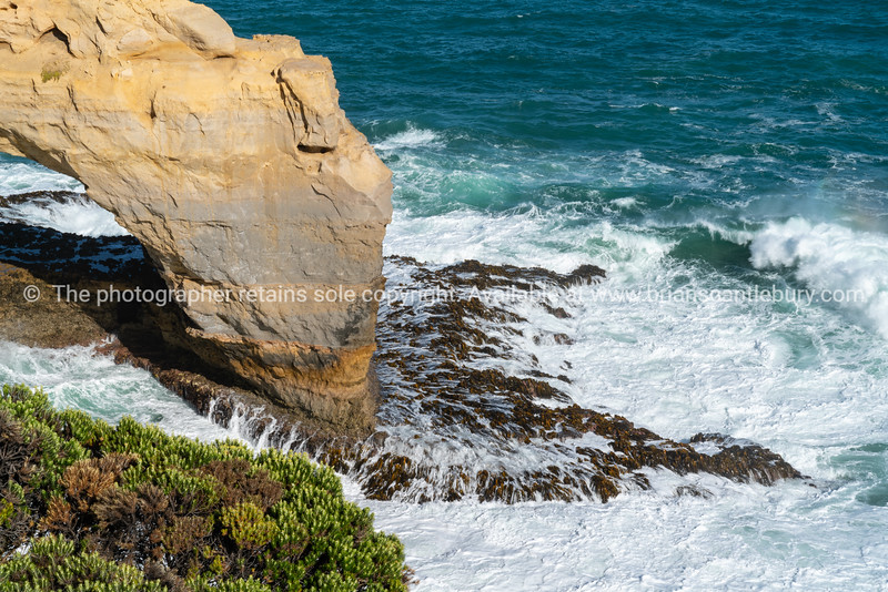 Coastal natural arch viewed from adjacent cliffs