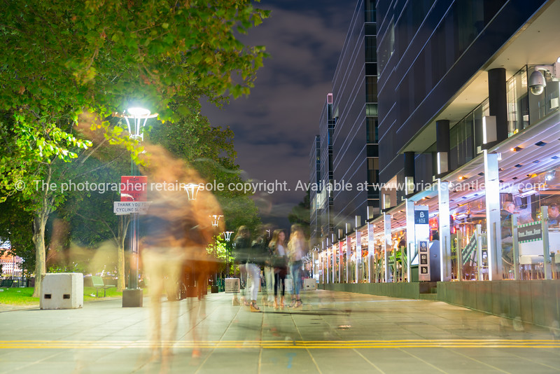 Ghostly effects of group of young woman on Southbank promenade outside Left Bank bar in long exposure at night.