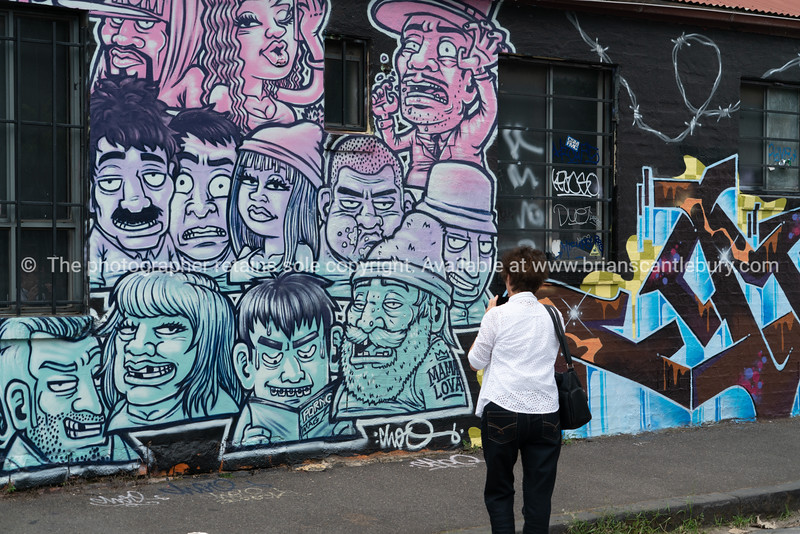 Tourist looking and passing inner suburb street art.