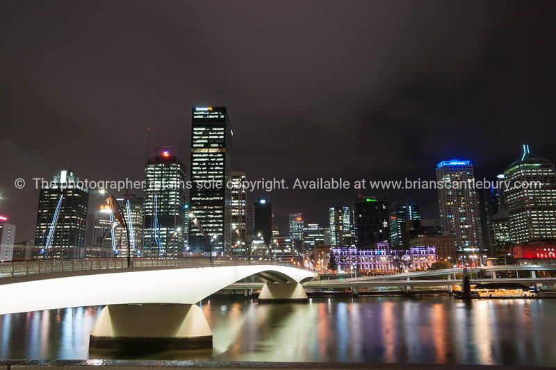 Brisbane Victoria Bridge iluminated against dark and city building lights
