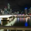 Brisbane Victoria Bridge iluminated against dark and city building lights