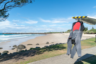 Black and red wetsuit hanging from back of vehicle drying in sun on Duranbah Beach, Coolangatta.