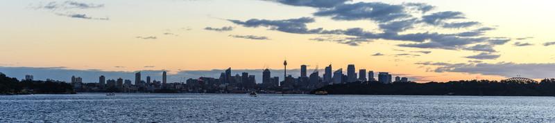 Sydney Skyline Panorama from Sydney Harbour National Park at dusk.