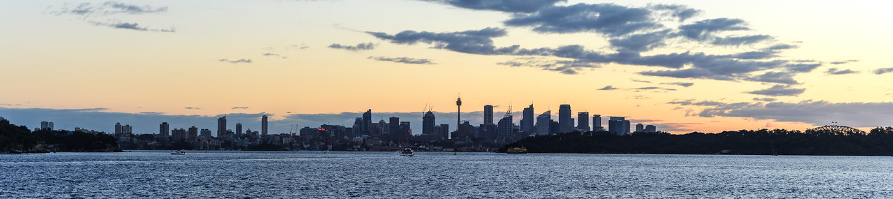 Sydney Skyline Panorama from Sydney Harbour National Park at dusk.