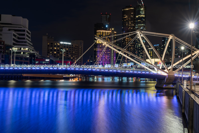 View down Yarra River towards Seafarers Bridge and lights of city buildings in long exposure,