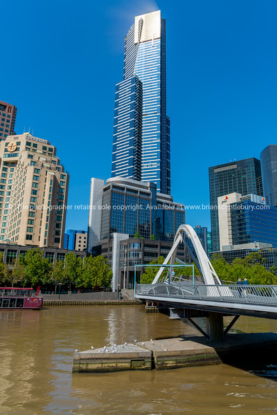Modern style Evan Walker Bridge leads across Yarra River to Southbank and tall Eureka Tower.