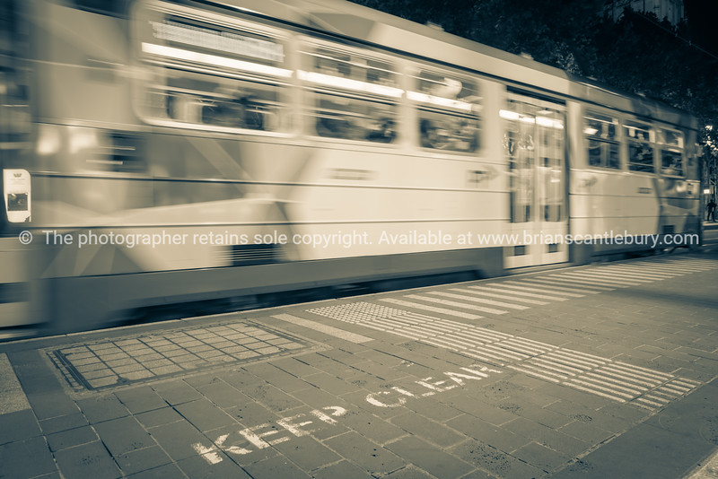 Blurred image of city tram whizzing past keep clear sign on pavement