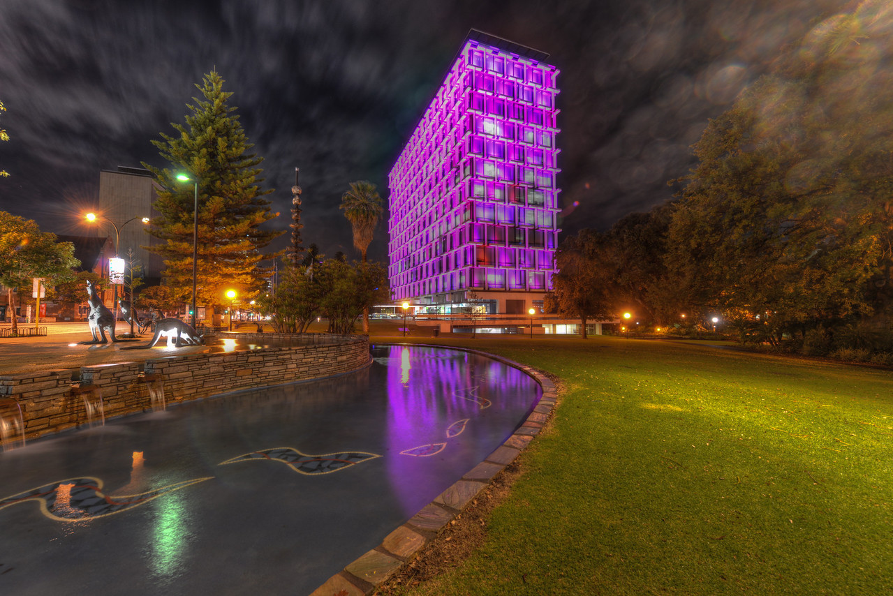 Council House in Perth. A 13-story office building set beside Stirling Gardens on St Georges Terrace in Perth, Western Australia. It is illuminated by LEDs at night and built in the modernist style.