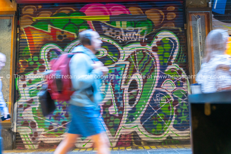 Woman blurred in motion walking past closed roller door of business
