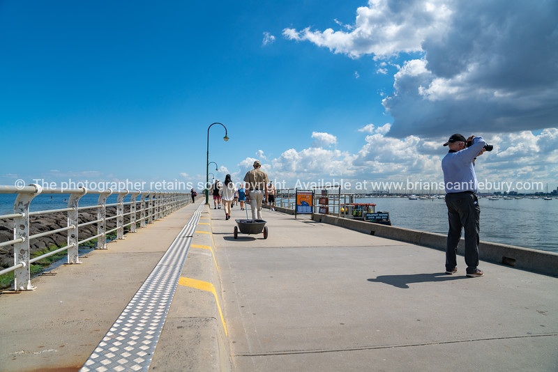 St Kilda pier with tourists and people walking out and returning from the kiosk on end of long pier.