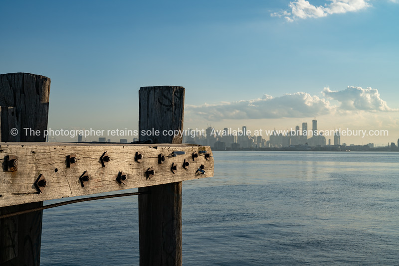Wharf piles and beams at end of dock with CBD skyline of Melbourne in background across harbour.