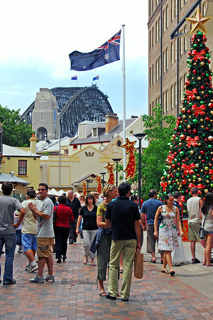 "Merry Christmas from Sydney<br /> <br /> This is what shopping in ""The Rocks"" in Sydney looks like a few weeks before the big day. Christmas time is much more relaxed (with a lot less apparel than I'm used to, at this time of year).<br /> <br /> I shot this during a visit to Sydney in 2006.  The biggest problem with this shot was having the area, reasonably clear of people, and timing this with the wind, so the flag stood out over the Sydney Harbour Bridge.<br /> <br /> Merry Christmas from Sydney."