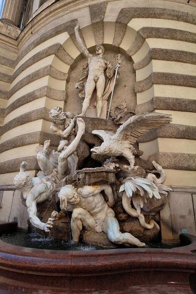 Numerous large statues and this fountain adorn the Imperial Building of the Hofburg Palace, Vienna, Austria.