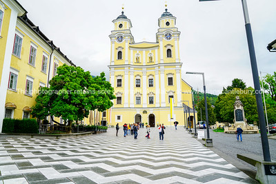 people walk in front of St. Michael Basilica on zigzag patterned cobblestone path leading to entrance.