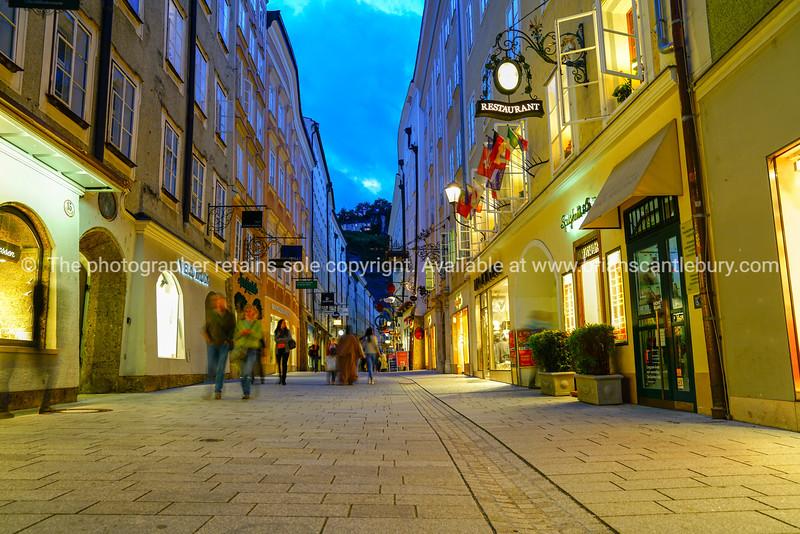 Street scene, people walking along narrow road between tall traditional buildings in old town.