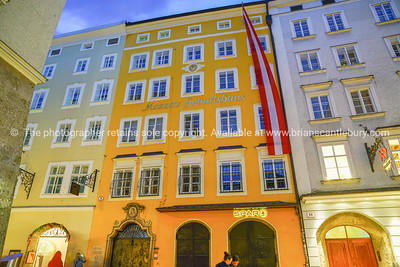 historic building that was home of Mozart from street below at night illuminated by street lights.