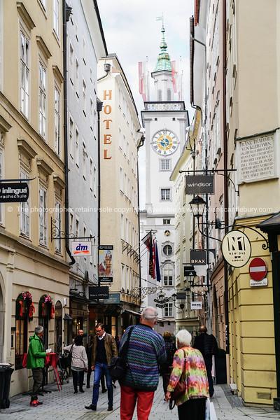 Street scene, people walking along narrow raod between tall traditional buildings in old town.
