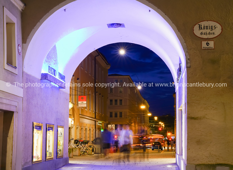 SALZBURG, AUSTRIA - SEPTEMBER 6 2017; Urban night lights moving people and cars blurred through brightly lit archway in old town retail tourist area