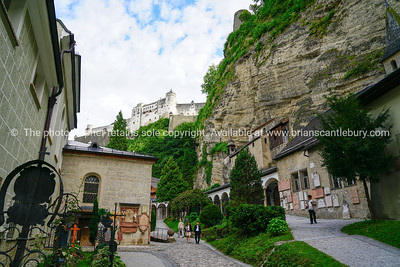 Tourists on converging paths between luxuriant cemetery gardens and graves and St. Peter's church  with  Hohensalzburg Castle on hill behind and catacombs