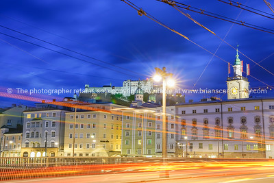 Horizontal light trails of moving vehicles and old town Salzburg