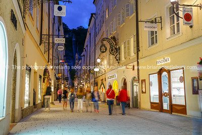 Street scene, people walking along narrow road between tall traditional buildings in old town.