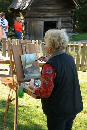 An art student painting the Cable Grist Mill.