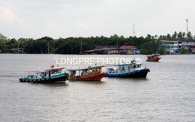 TUGS on river, tugging large ship