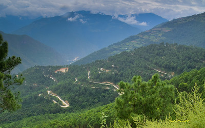 With this the typical road, it takes over three days to drive across Bhutan. Driving is quite a challenge as the roads turn about every 8 seconds even driving at 25 to 30 MPH.