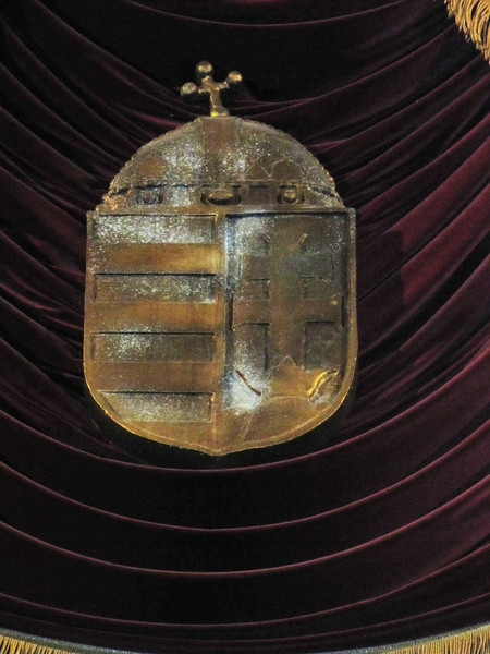 36-An early version of the Hungarian Coat of Arms hangs near the top of the proscenium.
