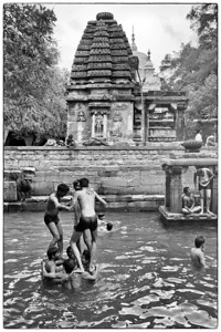 "Kids having fun playing in the Papavinasha Tirtha (""Tank of Ablution"") in Mahakuta.  Also seen are the Mahakutesvara temple (painted white) in the dravida style (rear) and Sangamesvara temple in nagara style (front)"