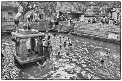 "Kids having fun playing in the Papavinasha Tirtha (""Tank of Ablution"") in Mahakuta."
