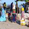 Brightly clothed women carry on their head fish purchased from fishermen early one morning in Bagamoyo.