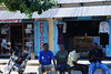 "Residents of Bagamoyo cool off mid-day in the shade in front of some ""dukas"" (shops)."